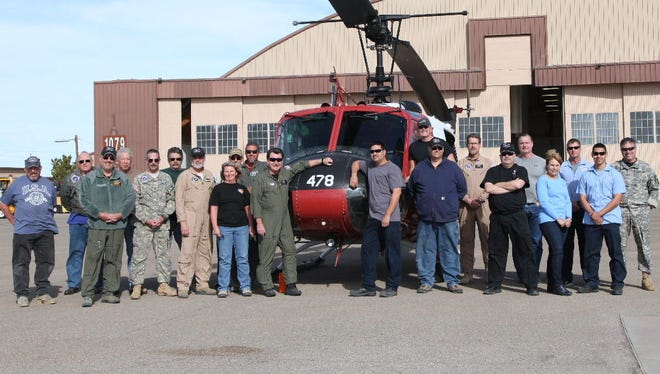 The White Sands Missile Range U.S. Army Flight Crew poses for a photo in front of the last Huey in the Army before it was transferred over to the Louisiana State Police.
