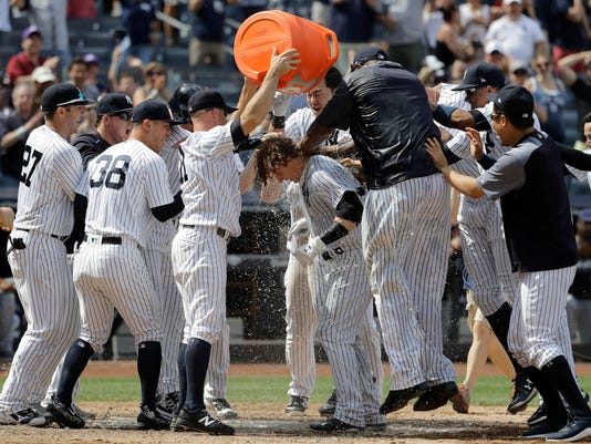 New York Yankees' Brett Gardner (11) showers teammate Clint Frazier, center, after Frazier hit a three-run walkoff home run off Milwaukee Brewers relief pitcher Corey Knebel during the ninth inning of an interleague baseball game, Saturday, July 8, 2017, at Yankee Stadium in New York. The Yankees won 5-3. (AP Photo/Julio Cortez)