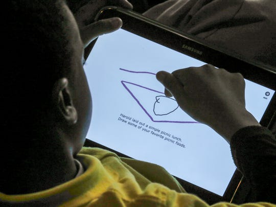 A student at one of three elementary schools uses at tablet to create art as part of the Stage One performance of Harold and the Purple Crayon at the Kentucky Center.
