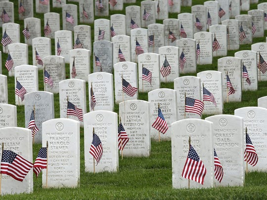 American flags are shown after being placed by members of the 3rd U.S. Infantry Regiment at the graves of U.S. soldiers buried at Arlington National Cemetery, in preparation for Memorial Day 2015 in Arlington, Virginia.