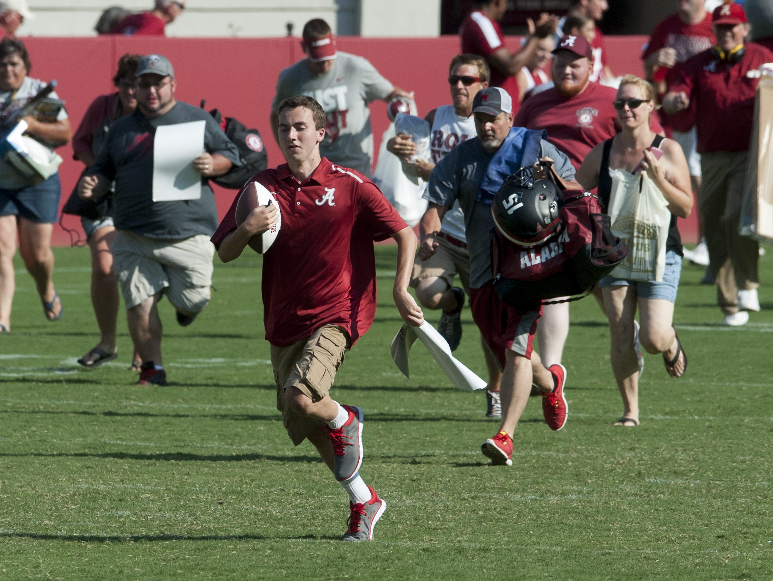 Fans race across the turf to get autographs during the University of Alabama fan day at Bryant-Denny Stadium in Tuscaloosa, Ala., on Sunday August 9, 2015.