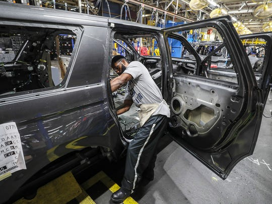 A worker at Kentucky Truck Plant installs wiring in a new vehicle as redesigned Ford Expeditions and Lincoln Navigators are rolling off the assembly line.October 27, 2017