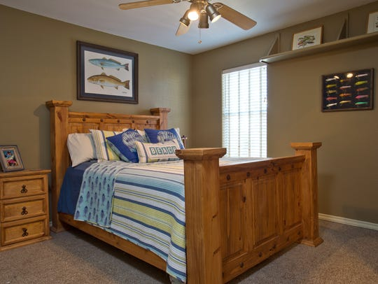 An upstairs guest room decorated in a fishing theme,