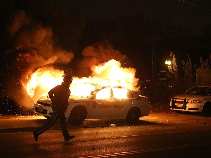 FERGUSON, MO - NOVEMBER 24:  A police officer runs