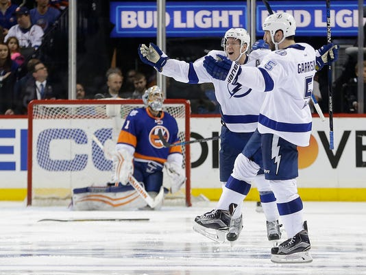 Tampa Bay Lightning defenseman Jason Garrison (5) and left wing Ondrej Palat (18) celebrate after Garrison scored the winning-goal in overtime against New York Islanders goalie Thomas Greiss (1) during the overtime period of Game 4 of the NHL hockey Stanley Cup Eastern Conference semifinals, Friday, May 6, 2016, in New York. The Lightning won 2-1. (AP Photo/Frank Franklin II)