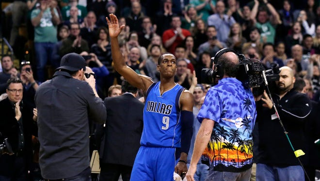 Dallas Mavericks guard Rajon Rondo (9) waves to fans and photographers, after a video presentation on his career as a member of the Boston Celtics, during a break after the first quarter of the Mavericks' NBA basketball game against the Boston Celtics in Boston, Friday, Jan. 2, 2015. (AP Photo/Charles Krupa)