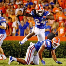 Matt Jones #24 of the Florida Gators jumps over Clay Burton #88 during the second quarter of the game against the Kentucky Wildcats at Ben Hill Griffin Stadium on September 13, 2014 in Gainesville, Florida.