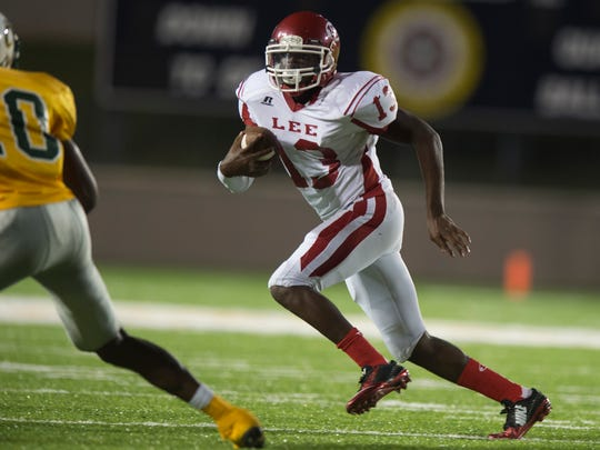 Lee quarterback Shaquille Johnson runs around the corner during the game between Lee High School and Carver High School on Thursday, Aug. 27, 2015, at the Cramton Bowl in Montgomery, Ala.