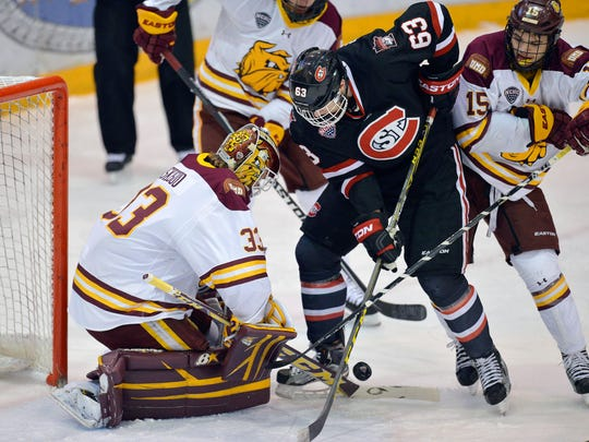 St. Cloud State's Patrick Russell (63) tries unsuccessfully to get the puck past Minnesota-Duluth goalie Kasimir Kaskisuo (33) while UMD's Willie Raskob (15) looks on in the first period Friday night at the Herb Brooks National Hockey Center in St. Cloud.