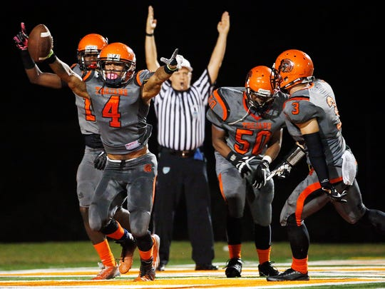 Lely's Kendall Duckworth (4) elates after a fumble returned for a touchdown with less than 10 minutes to play against Miami-Jackson Friday Nov. 14, 2014 at Lely High School. The Trojans held off the Generals 28-25 for the first post season victory since 1987. (Corey Perrine/Staff)