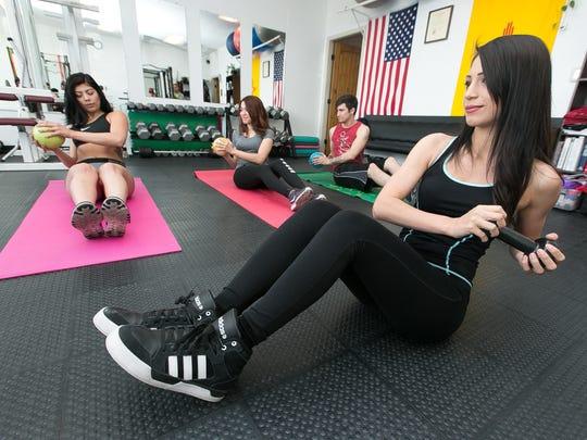 Melissa Anciaux, foreground, leads a pilates/yoga class