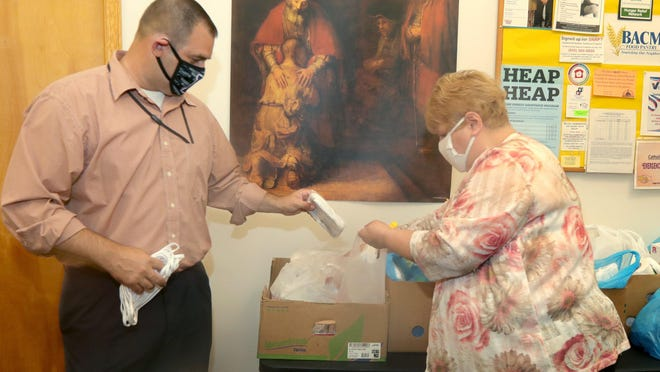 Barberton Mayor William Judge helps Barberton Area Community Ministries Executive Director Dorothy Suchka-Somerville place donated masks into food donation bags on Tuesday, Aug. 25, 2020, in Barberton, Ohio.