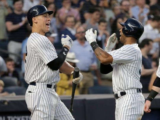 New York Yankees' Aaron Hicks, right, celebrates his two-run home run with Aaron Judge during the fifth inning of a baseball game against the Seattle Mariners at Yankee Stadium Tuesday, June 19, 2018, in New York.