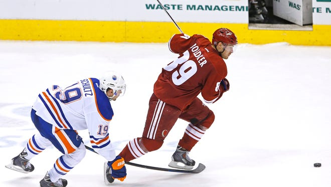 Arizona Coyotes left wing Mikkel Boedker (89) steals the puck from Edmonton Oilers defenseman Justin Schultz (19) on his way to score an empty net goal during the third period of their NHL game Wednesday, Oct. 15, 2014 in Glendale, Ariz.  The goal marked Boedker 's first career hat trick.