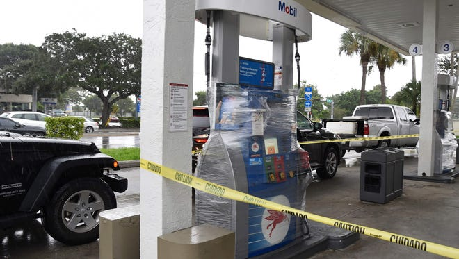 A gas station's pumps are wrapped and closed in Miami on Thursday.