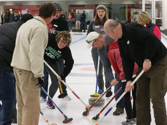 Instructor Lindsey Wolf (rear right) talks a group of students through how to sweep the ice in front of the curling stone during lessons at Milwaukee Curling Club in Cedarburg.