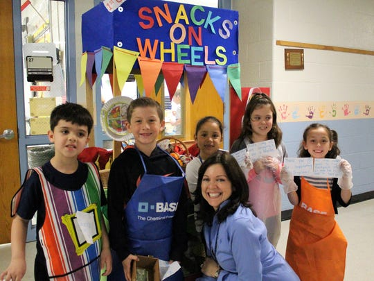 From left, Angelo. L. Tomaso School first- graders Miguel Gomes, Marc Drews, Leila Romero, Haylie Tremper, Charlotte Manzo are joined by their teacher, Elena Marinello, as they roll their healthy snack cart through school hallways on May 25.