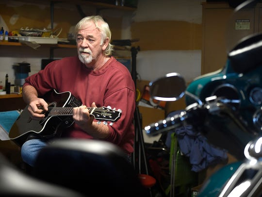 Retired heavy equipment operator Tom Clark is also a musician. Clark strums his guitar in his garage in Lebanon.