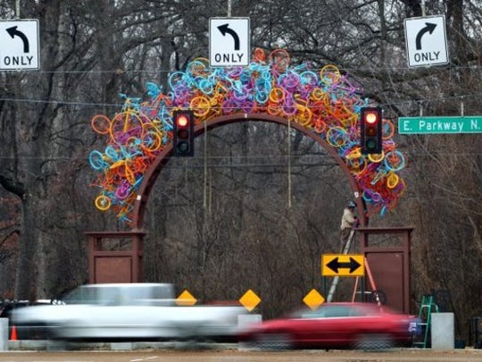 Traffic on East Parkway at Sam Cooper Boulevard speeds past the massive arch of used bikes designed by sculptor Tylur French. The sculpture is composed of more than 300 used bikes.