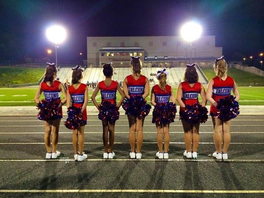 The West Henderson cheerleading team stands under the