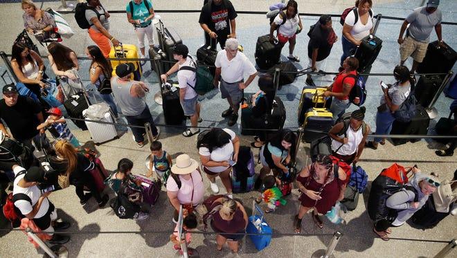 People wait in line June 29, 2018, to check in at McCarran International Airport in Las Vegas.