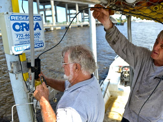 Jerry Corsaut (left), Ocean Research and Conservation Association field technician and Paul Zobel, installation assistant, adjust  the dissolved oxygen monitor that sits on top of a Kilroy. (FILE PHOTO)