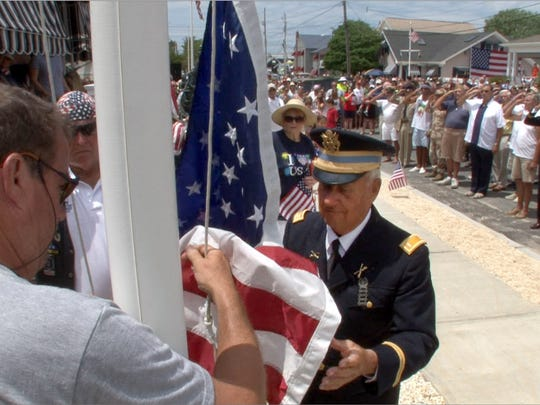 Army veteran Bob Morzek, Normady Beach, prepares to raise the flag during a ceremony on 6th Avenue in the Normandy Beach section of Brick Township, NJ, Monday, July 4, 2016.
