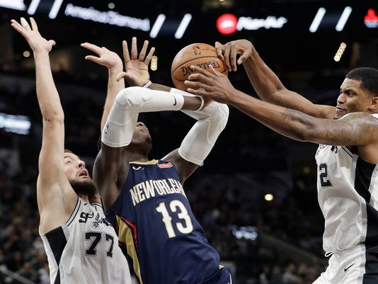 New Orleans Pelicans forward Cheick Diallo (13) is blocked, on a drive to the basket, by San Antonio Spurs defenders Rudy Gay (22) and Joffrey Lauvergne (77) during the first half of an NBA basketball game Wednesday, Feb. 28, 2018, in San Antonio. (AP Photo/Eric Gay)