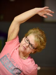 Tammy Habiger stretches during a yoga class Wednesday,