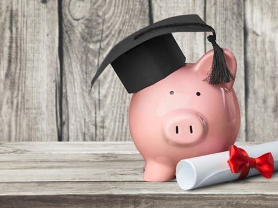 Piggy Bank wearing a graduation cap next to a rolled-up diploma