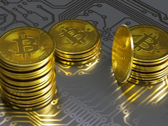 Physical gold bitcoin stacks on top of a gray circuit board.