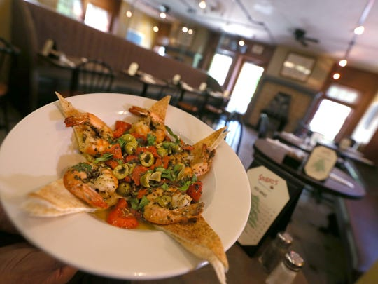 Ganbari, a dish of sautŽed shrimp served on pita triangles with roasted peppers and olives, is served up in the main indoor dining room at Sinbad's Mediterranean Cuisine on Park Avenue in Rochester.