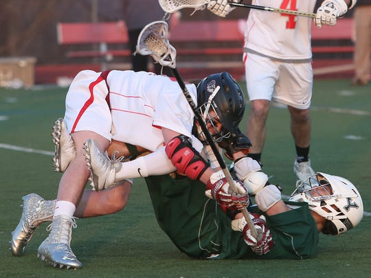 From left, Somers' Luke Roediger (17) hits Yorktown's Kristopher Alvarado (9) during a boys lacrosse game at Somers High School April 10, 2014. Yorktown won the game 14-6.