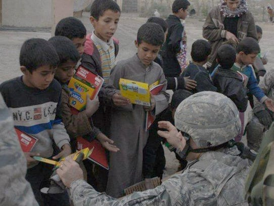 Master Sgt. Brent Baker hands markers and crayons to