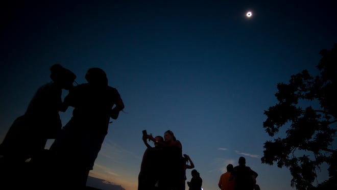 People watch the solar eclipse as it reaches totality at The Cove in Farragut on Monday, August 21, 2017.