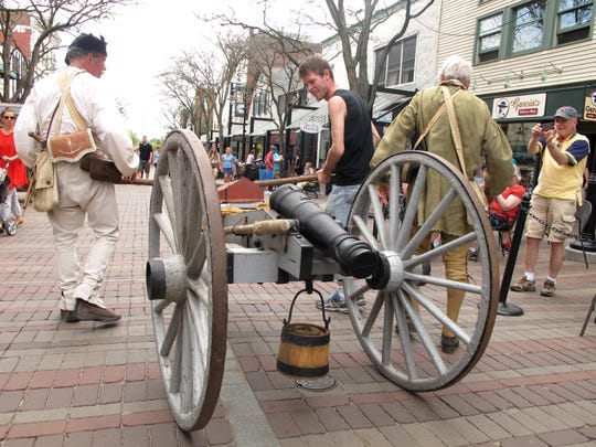A bystander joins reenactors from the Ethan Allen Homestead negotiate an antique cannon down Church Street in Burlington on Saturday.