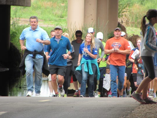 St. George Mayor Jon Pike, left, joins a group of well-wishers running on the heels of Ephraim resident Justin Osmond as Osmond completed a 250-mile journey to St. George's Confluence Park on Saturday as part of a benefit to raise funds and awareness for the hearing-impaired.