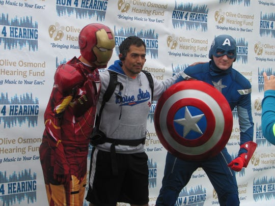 "Juan Freeman, center, poses with Ironman and Captain America actors Saturday during the ""Super Hear-O 5k Fun Run"" at St. George's Confluence Park."