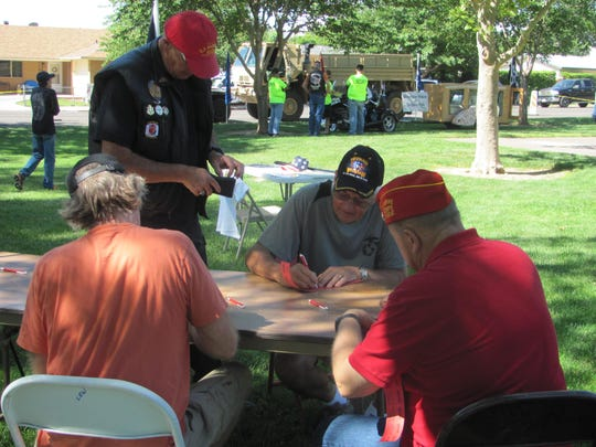 Attendees at the Help On The Homefront veterans benefit sign up for a prize drawing Saturday at Vernon Worthen Park. The event was designed to raise money for veterans who may need assistance with household repairs.