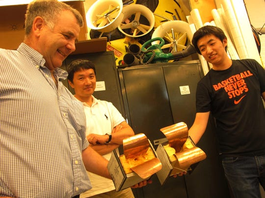 Displaying prototype antennae pieces for a ground-penetrating radar project are, from left, UVM School of Engineering professors Dryver Huston and Tian Xia; and graduate student Yu Zhang.