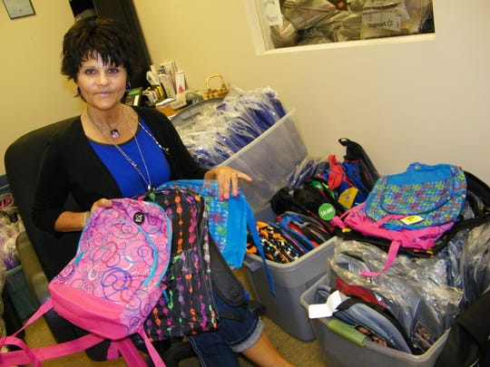 Maureen 'Moe' Saponari shows some of the dozens of book bags that were donated to the Ottawa County Salvation Army for the organization's annual Tools for School programs.