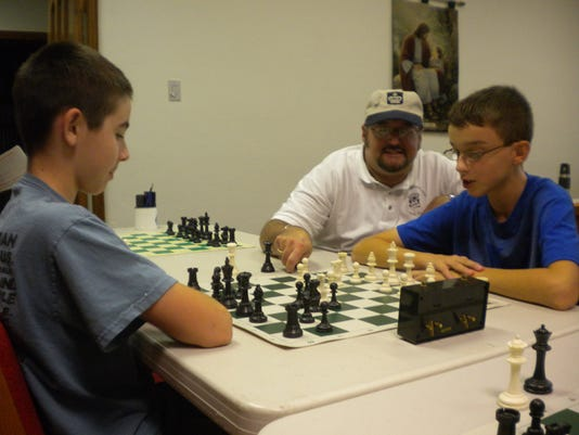 YHSA homeschool students Jimmy McAllister, left, and Al Mokris, right, participate in a homeschool chess club, as chess coach Mike Koplitz, pastor at Calvary York UMC, looks on. (Submitted photo)