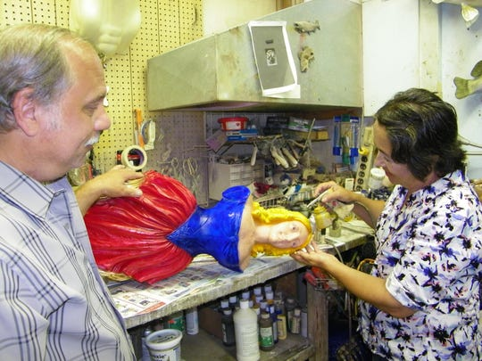 Mike Pusateri watches as his wife, Peggy, paints a ship figurehead. The couple's figureheads have been sold around the world, and one is featured in the Colonial American Exhibit at Universal Studios Japan.