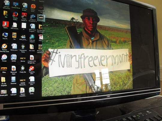 """An African wildlife ranger displays a sign with """"#IvoryFreeVermont"""" in a photo on the computer of Ashley Prout McAvey, a Shelburne resident and ivory-ban activist."""