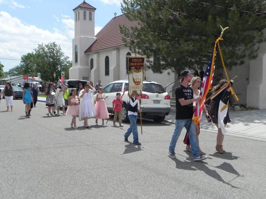 Locals take part in a parade past Holy Family Catholic Church as part of the Portuguese Festa after mass on Sunday.