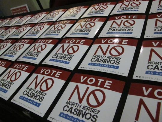 Stickers opposing a referendum on whether to allow two new casinos in northern New Jersey sit on a table before a rally in Atlantic City, N.J. on Thursday Oct. 27, 2016. The measure is designed to recapture gambling dollars being lost to casinos in neighboring states, but opponents say it could cause three of Atlantic City's seven casinos to shut down.(AP Photo/Wayne Parry)