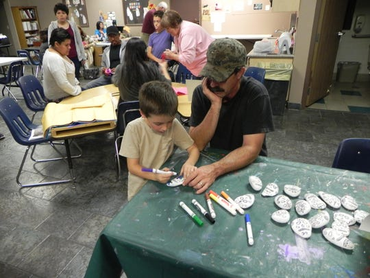 A child participates in rock decorating as part of Yerington Theater of the Arts' Day of the Dead celebration on Oct. 27.