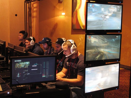Video game players compete against one another in an esports tournament at Caesars casino in Atlantic City. Casinos are slowly embracing esports as a way to help their bottom line, but so far, the money is coming from renting hotel rooms to the young players and selling them food and drinks, not from turning them into gamblers.
