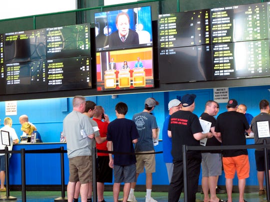 FILE - In this June 19, 2018, file photo, sports bettors line up at windows at Monmouth Park racetrack in Oceanport, N.J. With the legalization of sports gambling in the United States and its gradually expanding implantation, some in the industry are suggesting horse racing add fixed-odds wagering as a way to respond to the changing landscape, evolve and compete with the other options now available. (AP Photo/Wayne Parry, File)