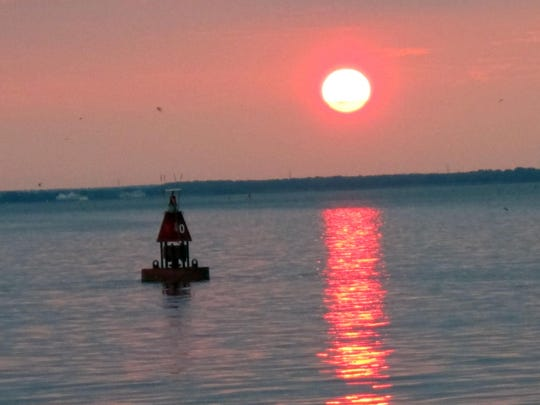 The sun sets over Barnegat Bay in Barnegat Light, N.J. New Jersey says it's giving $10 million to groups to carry out projects to prevent stormwater runoff pollution into the bay, one of the most ecologically challenged in the U.S.